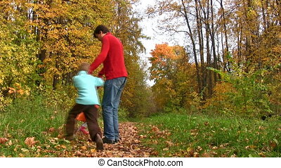 father rotate two children in autumn park