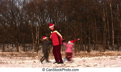 father rotating children in christmas hats