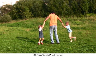 father rotating two children