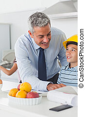 Father showing son his blueprints as he is wearing yellow helmet in the kitchen before work