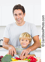Father showing son how to slice vegetables