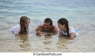 Father shows shell daughters.