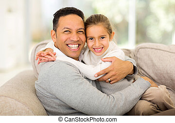 father sitting on the couch with his daughter