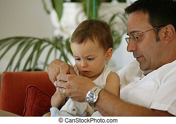 Father sitting on the sofa with toddler
