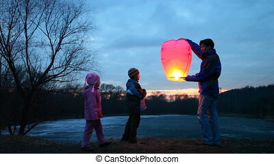 father, son and daughter start chinese lantern of winter forest, part2