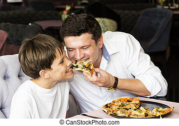 Father son eating an Italian pizza at a pizzeria