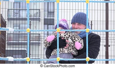 father spend freetime whit cute kid in playground at winter.
