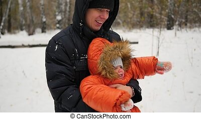 father spinning child in winter Park