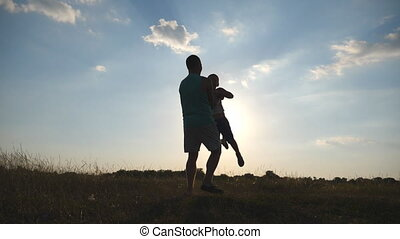Father spinning his little son in a meadow on a sunny day. Dad rotate baby around at nature. Family playing on the field at sunset. Daddy and child having fun together. Close up Slow motion