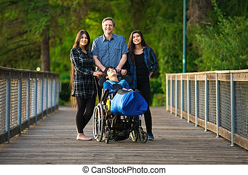 Father standing with biracial children on wooden bridge, special needs