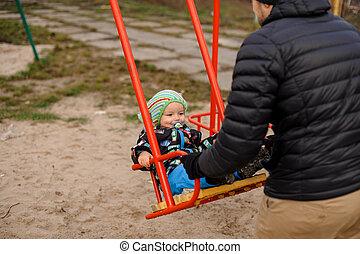 Father swinging baby boy in a swing