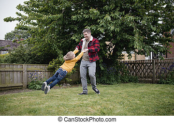 Father Swinging His Son Around Outside