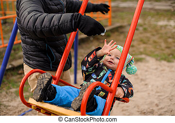 Father swinging toddler boy in a swing
