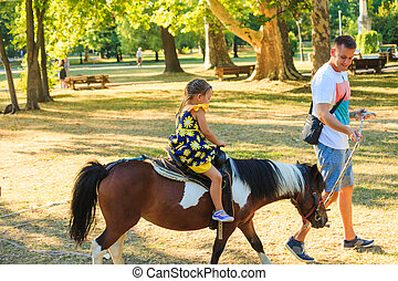 father take his little dother for a ride on pony horse in park