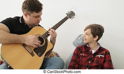 Father takes chords of the famous song on a guitar showing his son how to play slow motion