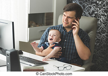 Father talking by phone and taking care of his baby
