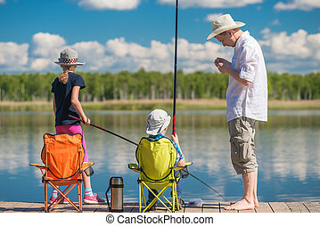 father teaches his children to fish on a fishing pole at the...