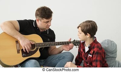 Father teaches his curious son to play the guitar slow...