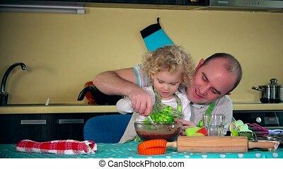 Father teaching adorable daughter to cake a bake. Family mix dough