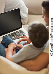 Father teaching boy in using laptop at home