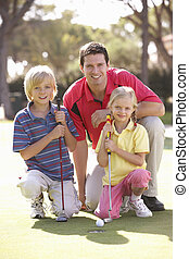Father Teaching Children To Play Golf On Putting On Green
