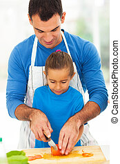 father teaching daughter cooking