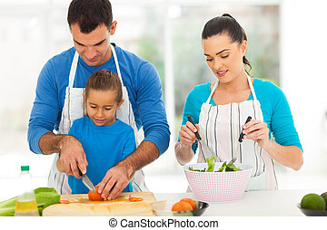 father teaching daughter cutting vegetables
