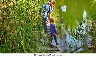 Father teaching daughter how to fish and bait.