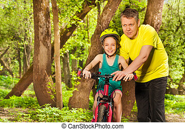Father teaching his daughter to ride a bicycle
