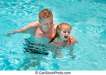 Father teaching his daughter to swim in swimming pool