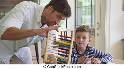Father teaching his son mathematics at table in a comfortable home 4k