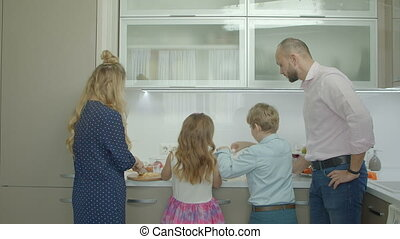 Father teaching siblings to prepare omelet in kitchen -...