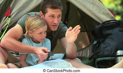 Father teaching son how using a map - Father showinng his...