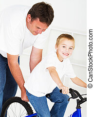 father teaching son ride a bicycle