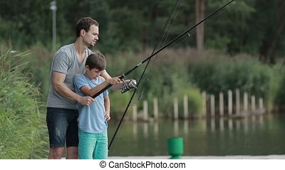 Father teaching son to fish at lakeside in summer