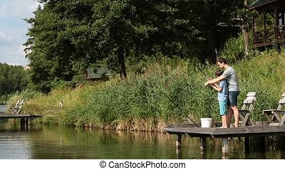 Father teaching son to fish at freshwater pond - Loving...