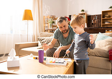 Father teaching son to paint