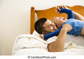 Father tickling child.