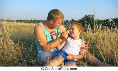 Father tickling his little son outdoor. Happy young man lying on grass at the field and playing with his baby boy. Cheerful daddy and his child having fun together in a park. Slow motion Close up