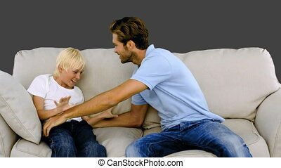 Father tickling son on the sofa on