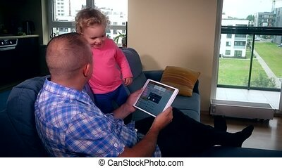 Father turn on music on tablet and happy active baby girl dance on sofa.