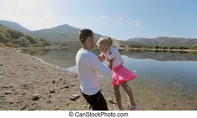 Father twirling his little daughter round in slow motion