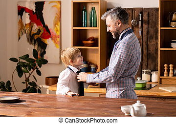 Father tying necktie to little son