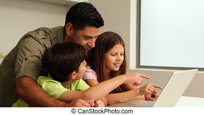 Father using the laptop with his children