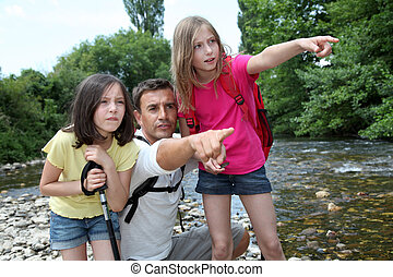 Father walking in river with kids
