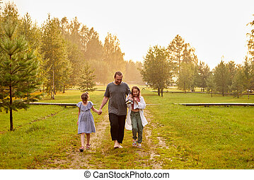 Father walking with daughters in countryside in sunset