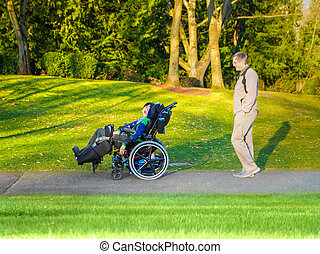 Father walking with disabled son in wheelchair at lake park