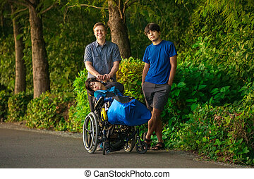 Father walking with two sons, special needs child in wheelchair