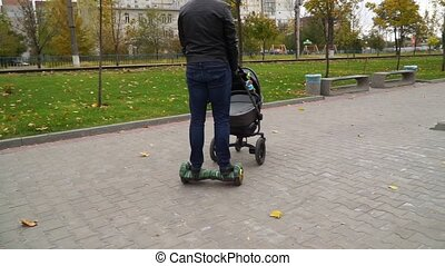 Father walks with a baby carriage and riding on a gyroscooter