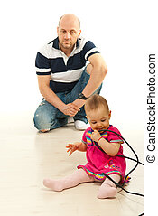 Father watching baby girl playing with cables